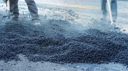 roadwork : Workers throw hot asphalt on the road. Compaction of pavement in road construction. Road repairing works