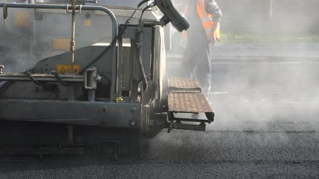 roadwork : Fresh hot asphalt on the new road. Road construction. Asphalt paver machine during road construction and repairing works. Workers in uniform background