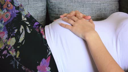 nascimento : Pregnant woman resting on couch and touching her belly Stock Footage