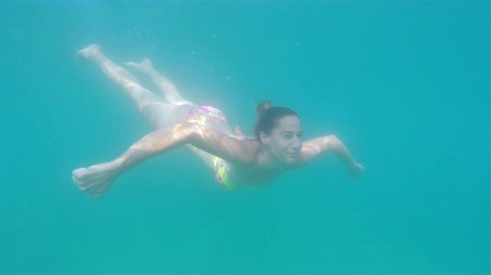 plavat : Woman in bikini swimming underwater slow motion