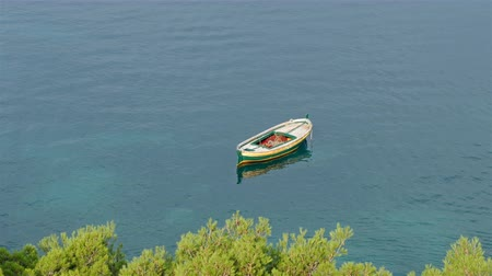 küçük sandal : Colorful small wooden boat on calm sea near coast with pine trees in the morning aerial view