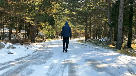 low angle shot : Young man with jacket and hood walking on the middle of frozen mountain road slow motion Stock Footage