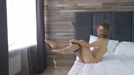 smyslnost : girl takes off her panties and sitting on the bed Dostupné videozáznamy