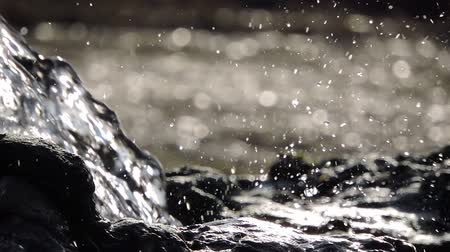 powódź : Water splashes over stones in sunlight, mountain waterfall, close up Wideo
