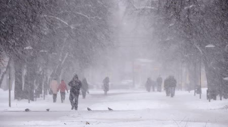 Snowfall in the city, people walking on snowy road. Blizzard, snowstorm