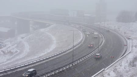 commute : Cars driving on snowy road in winter, traffic on highway in snowfall, blizzard