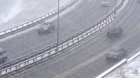 Cars driving on snowy road in winter, traffic on highway in snowfall, blizzard