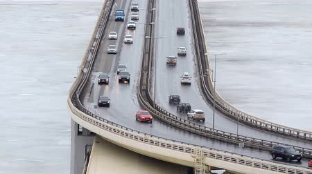 Cars driving on snowy road in winter, traffic driving on the bridge, highway