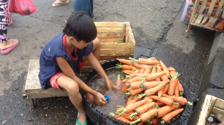 emek : Underage labor boy cleaning vegetables in an Asian market. Stok Video