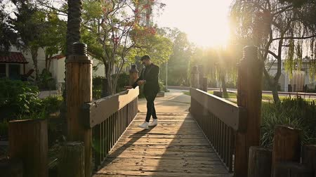 casual wear businessman : Handsome hot young male of middle-eastern ethnicity walks on a bridge, backlit