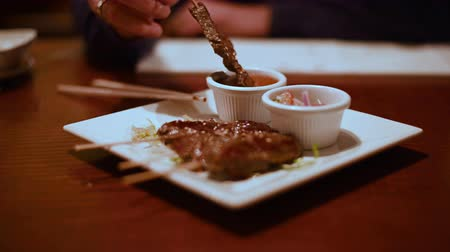 dips : Person at restaurant table dips Japanese beef skewers in sauce