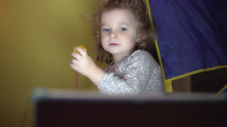 tablet bilgisayar : Little girl playing with toys and watching the tablet