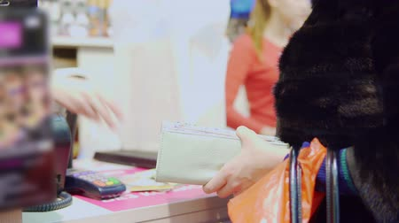 purse : A young woman paying in the store using payment card Stock Footage