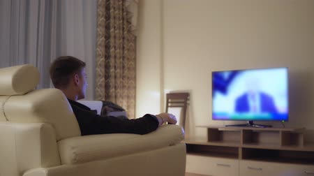 armchairs : Attractive young man watching television Stock Footage