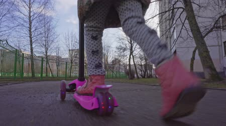 chodnik : Little girl is riding a scooter
