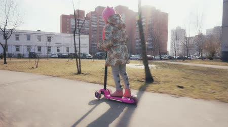 bruk : Little girl is riding on a scooter on a sunny day in the spring Wideo