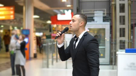 громкоговорители : A young attractive man showing a show in a shopping center. He singing into the microphone Стоковые видеозаписи
