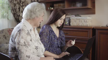 孫娘 : A young woman is teaching her grandmother to use a laptop and making purchases on the Internet. 4K 動画素材
