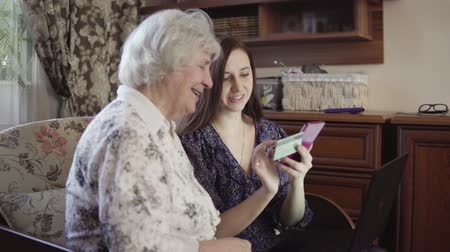 use laptop : Young woman is teaching grandmother to make purchases and payments through the Internet on a smartphone. 4K Stock Footage