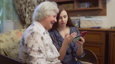 孫娘 : Young woman is teaching grandmother to make purchases and payments through the Internet on a smartphone. 4K 動画素材