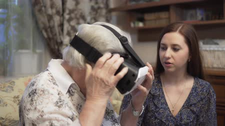 talk show : Granddaughter is showing grandmother virtual reality glasses. An elderly woman for the first time uses virtual reality glasses. 4K Stock Footage