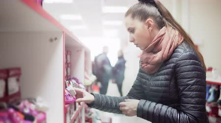 comparar : Young attractive woman is choosing childrens shoes in a store. She is looking at the childrens shoes and comparing them. 4K