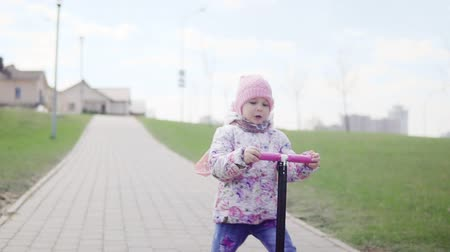 skútr : A child is riding a scooter on a sunny day. Slow motion