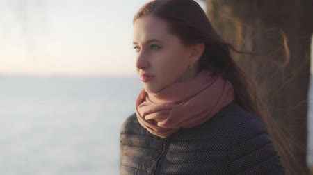goes : A woman walks along the lake at sunset. Slow motion Stock Footage