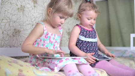 segít : Little girls play on the tablet and phone. 4k Stock mozgókép
