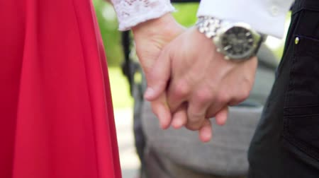 megbízható : A man holds a womans hand while walking. Slow motion. Close-up