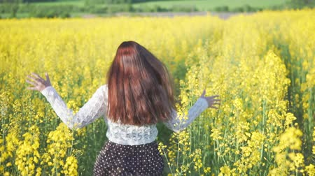 kolza tohumu : Young attractive girl running on a rapeseed field