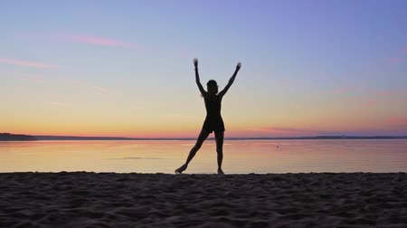 spor ayakkabısı : Young woman is runing along the beach on a sunset background Stok Video