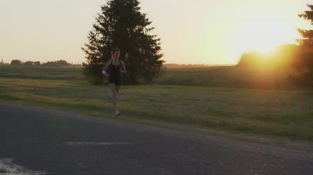 dedicação : Young woman runner is running down the road in a sporty uniform