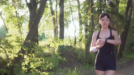 oran : Young athlete runner is runing in the park and looking at the heart rate monitor Stok Video