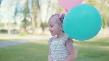 saadet : A little girl is running in the park with balloons
