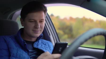 хорошее настроение : A man uses a mobile phone while driving a car.