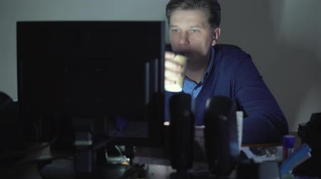 vyčerpání : A man is drinking coffee in the office at night at the computer.