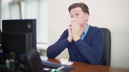 influenza : the man blows his nose at the office