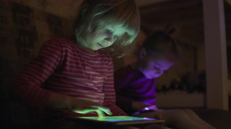 mobile game : Children use the mobile phone at night. Stock Footage