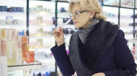 perfume bottle : A middle-aged woman is choosing perfume in a store Stock Footage