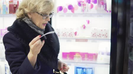 perfumy : A middle-aged woman is choosing perfume in a store Wideo