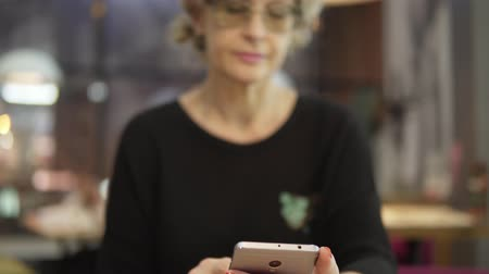 в середине : A middle-aged woman uses mobile phones in a cafe.