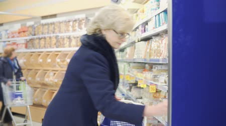 supermarket food : woman buys milk in a bottle in a store