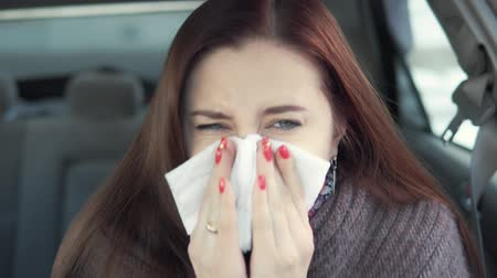 üfleme : a woman blows her nose in the car Stok Video