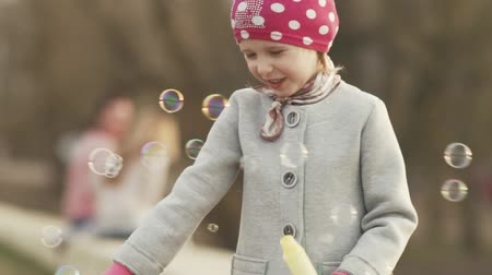 невинный : Little girl blows soap bubbles at sunset.