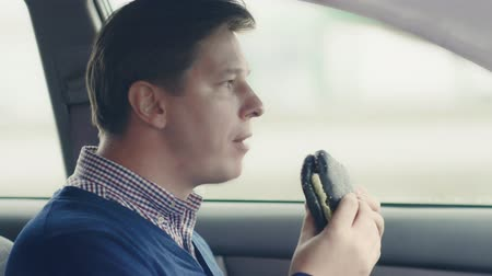 smak : A man is eating a hamburger in the car. Fast food. Wideo