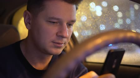 Young male using mobile phone in the car in the evening Wideo