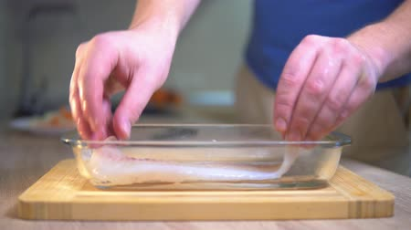 A man puts a glass dish fish. Cooking fish