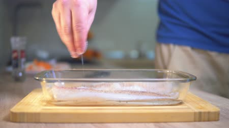 Man sprinkles salt on fish. Cooking fish