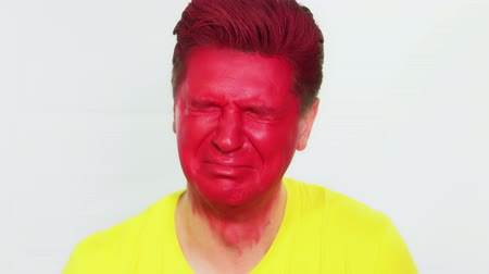Man crying. Red color male face. Bright portrait of a man close up on a white background Wideo